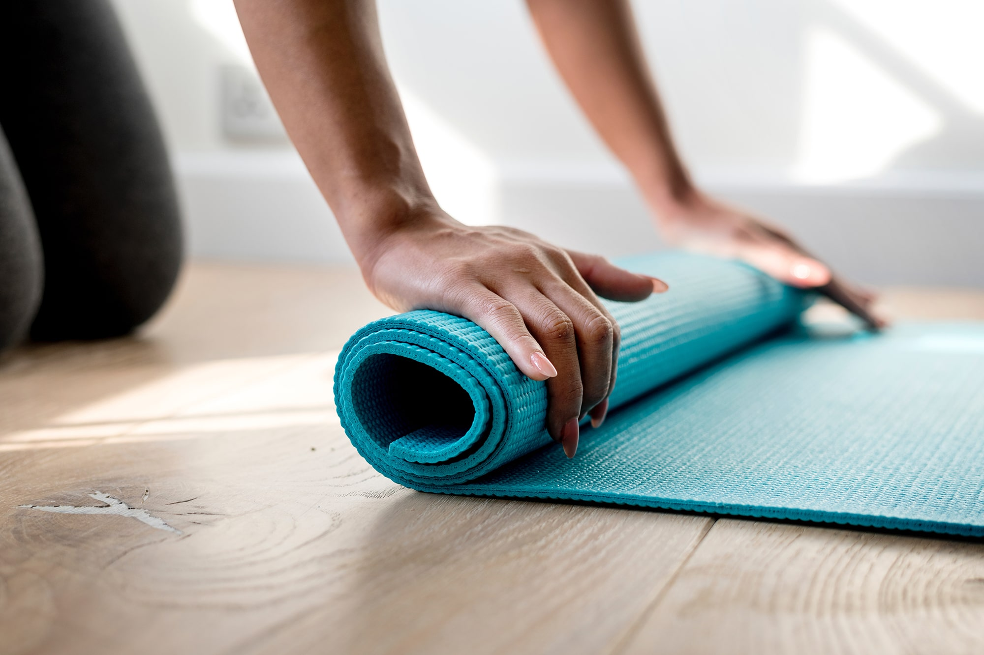 woman rolling yoga mat