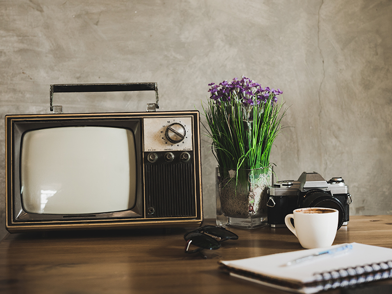 old tv, camera, coffee and notebook with pen on a wooden table