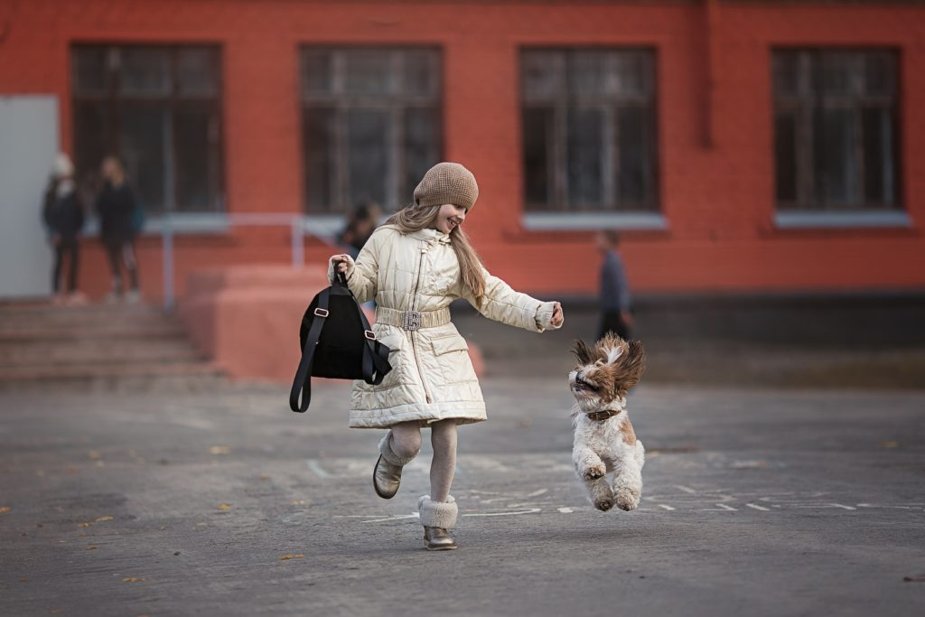 kid happily walking with the dog
