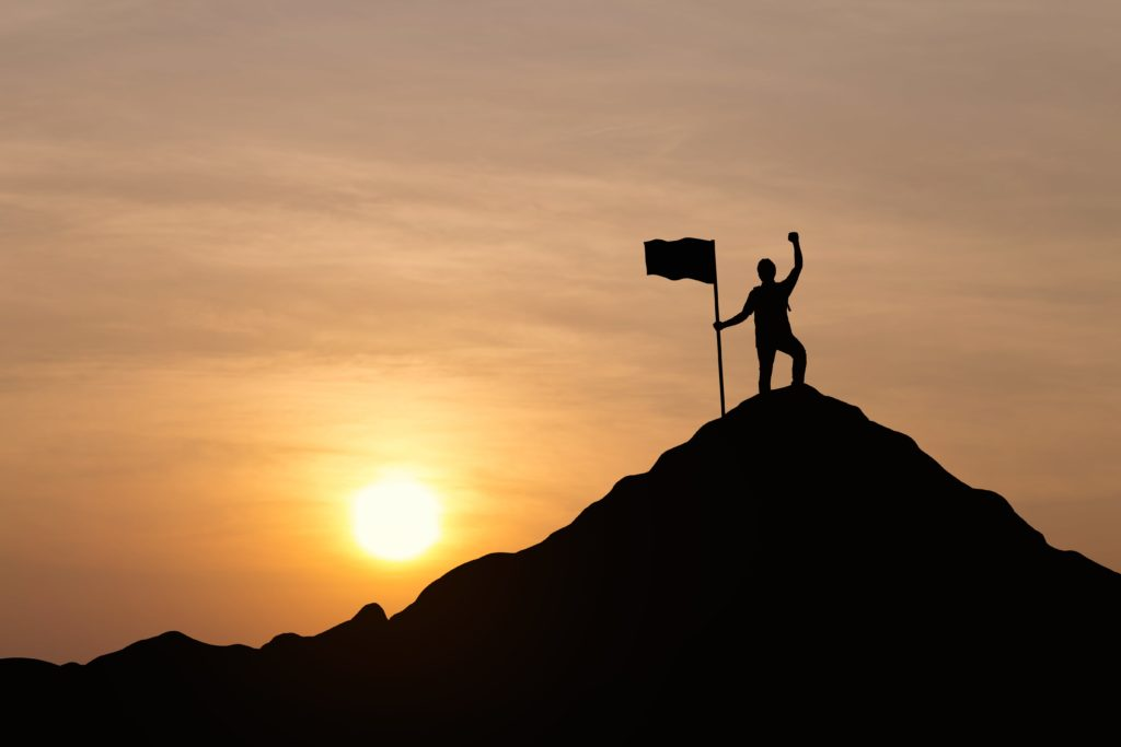 silhouette of Man holding flag on top of a moutain