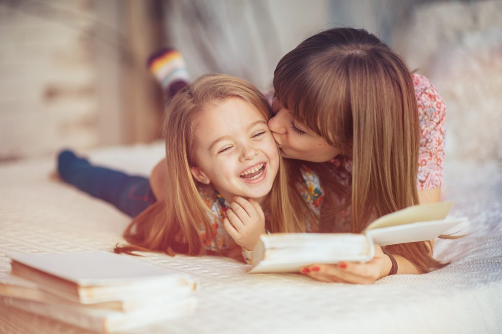 mom kissing daughter on cheek while holding a book