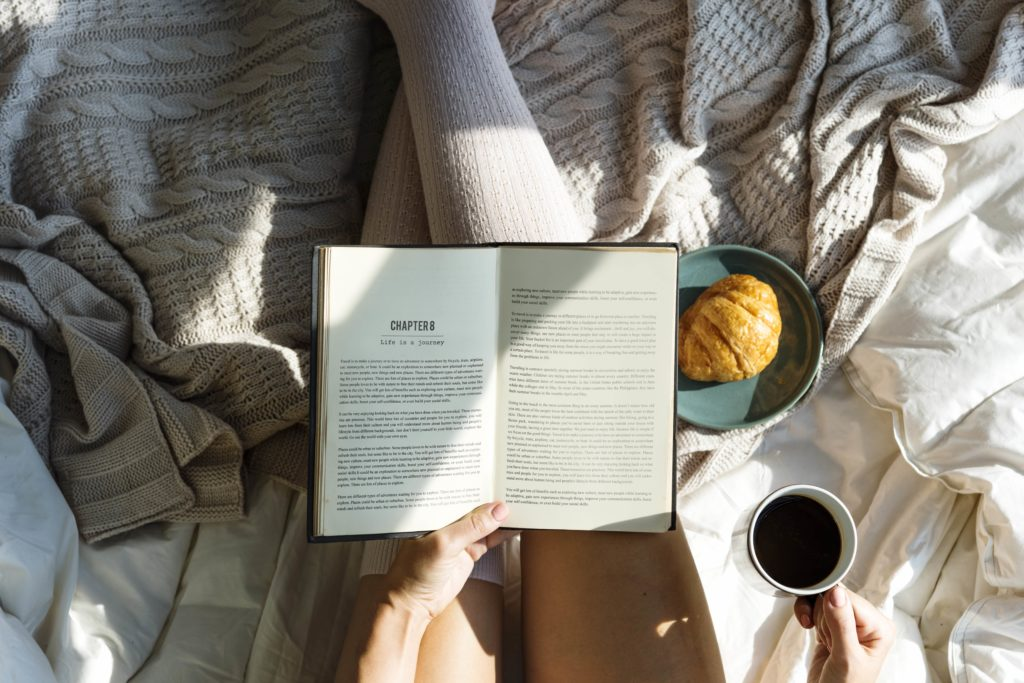 woman reading book on bed coffee on one hand